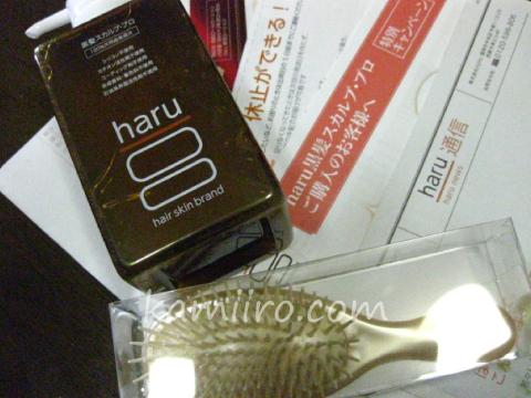 通販で届いたharu黒髪スカルプ・プロと特典のブラシ。パンフレット類を撮影した写真