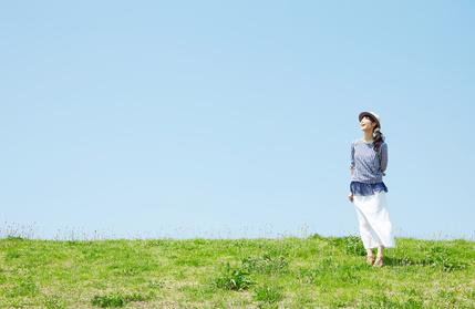晴れた日に丘にたたずむ女性