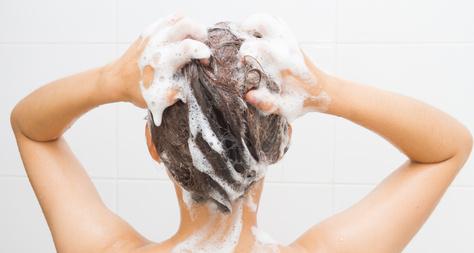 シャンプーで頭を洗う女性