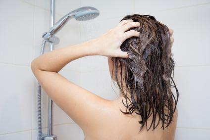 シャンプーを洗い流している女性