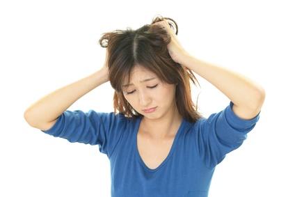 ベタベタする髪に頭を抱える女性