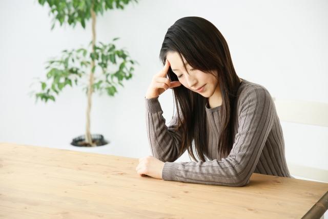 テーブルに肘をつき頭痛にうなだれる女性