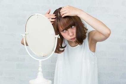 頭皮の赤みを鏡でチェックしている女性