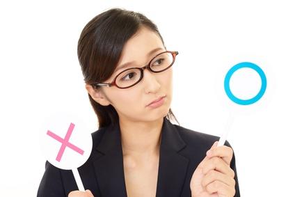 〇と×の札を持つメガネの女性