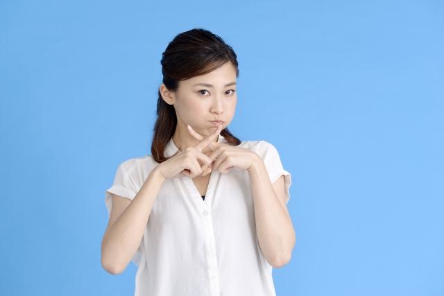 人差し指で×を表す女性