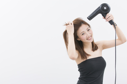 ドライヤーで髪にボリュームをつけている女性