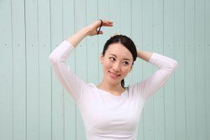 髪を後ろで束ねようとしている女性
