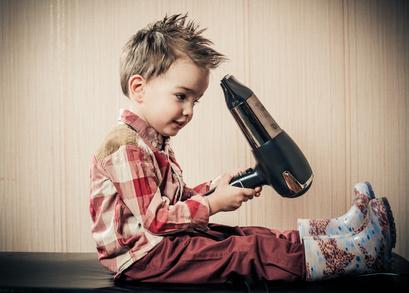 ドライヤーでヘアセットする小さな少年
