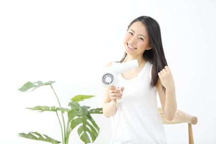 ヘアドライヤーで髪を乾かす笑顔の女性