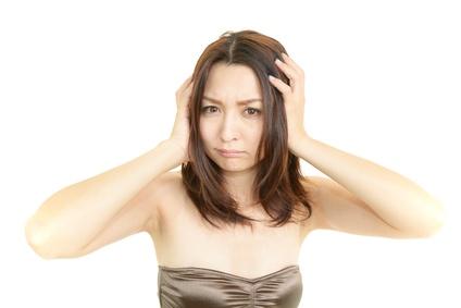 ベタつく髪に頭を抱える女性