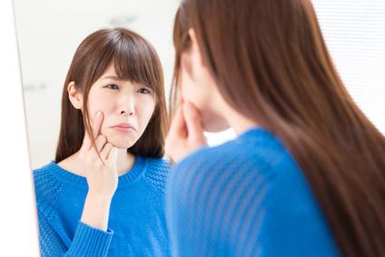 鏡を見て肌荒れにショックを受ける女性