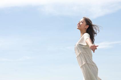 南風に吹かれて爽快な笑顔の女性
