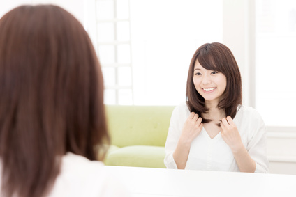 まとまりある髪を鏡でチェックして満足げな女性