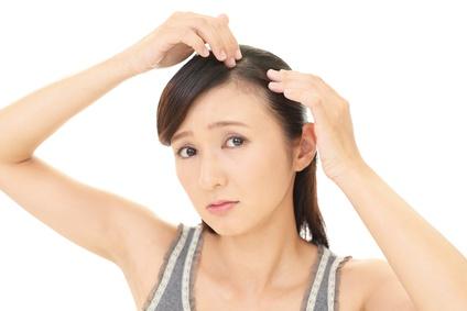 フケが気になって頭皮を指先で確認する女性