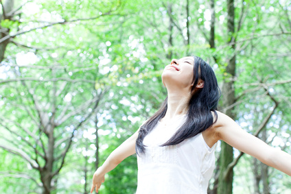 森の中で両手を広げ深呼吸する女性
