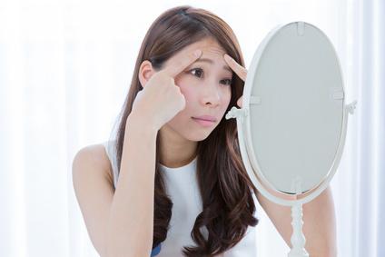鏡の前で額のシワを気にする女性