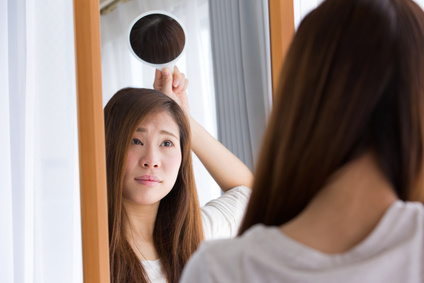 合わせ鏡で後頭部をチェックする女性