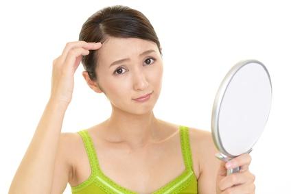 手鏡を持って生え際の薄毛を気にしてる女性