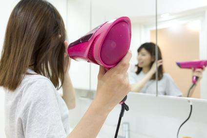 洗面台でドライヤーをかける女性