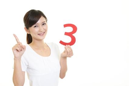 数字の3を持ち人差し指を指す女性