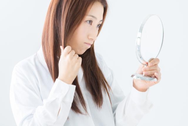 手鏡を見ながら髪ダメージを気にする女性