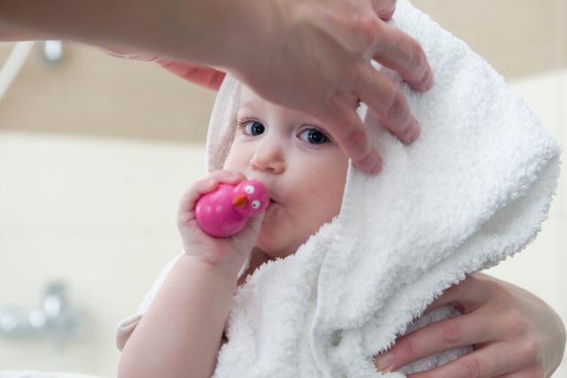 お風呂上り頭を拭いてもらう赤ちゃん