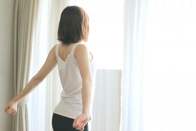 窓辺で日差しを浴びながら背筋を伸ばす女性