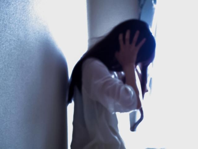 壁際で頭を抱える女性