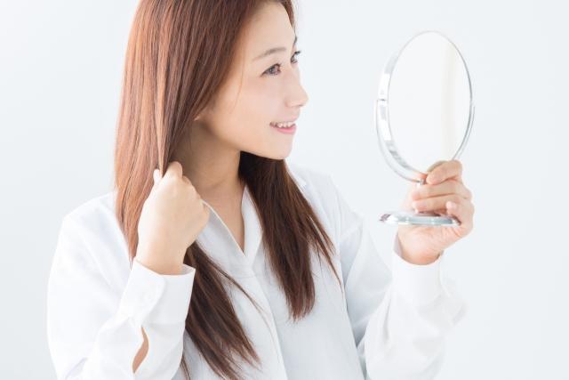 手鏡を持ちながら髪を触る女性