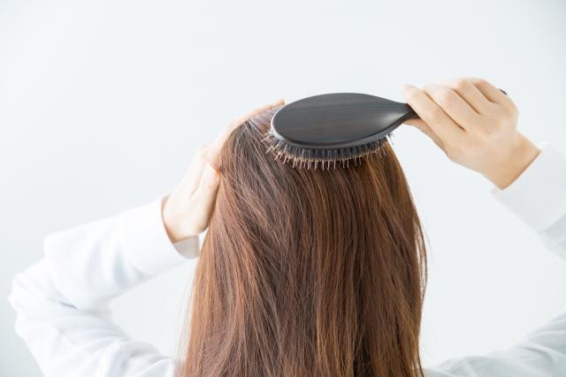 ヘアブラシで頭皮マッサージをする女性の後ろ姿