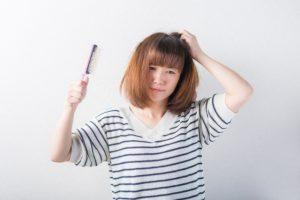 パサパサした髪をブラッシングで何とかしようとする女性