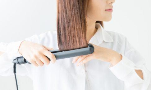 ヘアアイロンで髪を整えている女性