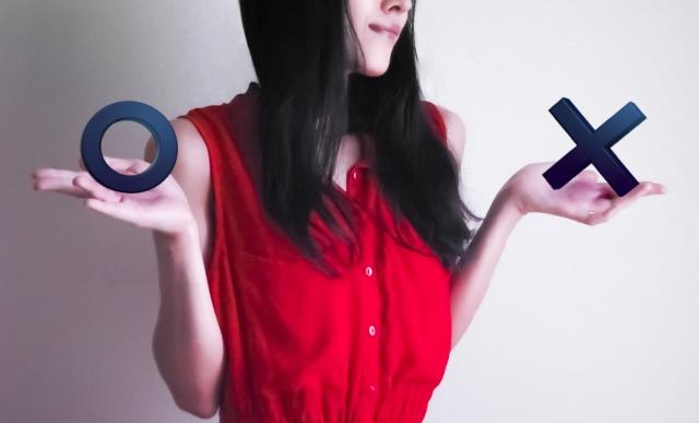 ○と×を持つ赤い服の女性
