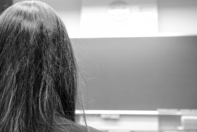 髪が傷んでいる女性の後ろ姿。モノクロ写真