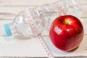 メジャーを巻いたペットボトルとリンゴ