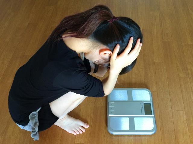 体重計を見て頭を抱えしゃがみ込む女性