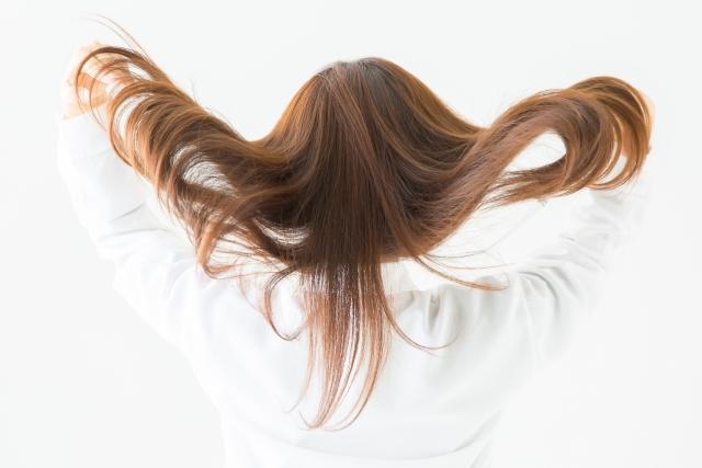後ろ髪をフワッとかき上げる女性