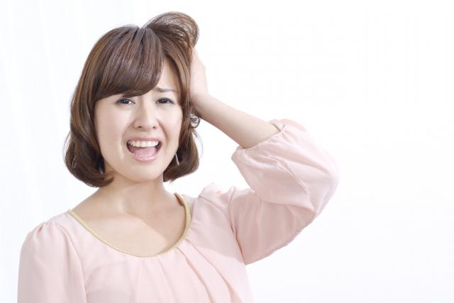頭を抱え嘆く女性