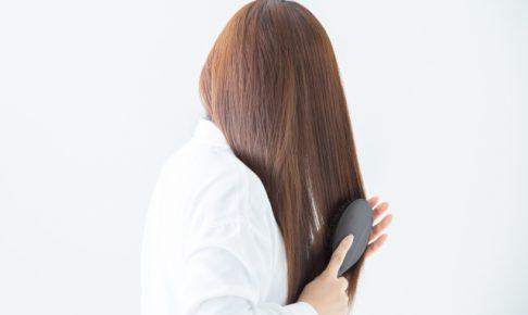 ブラシでロングヘアをとかす女性の後ろ姿
