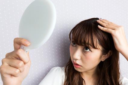 手鏡を持って頭皮をのぞき込む女性
