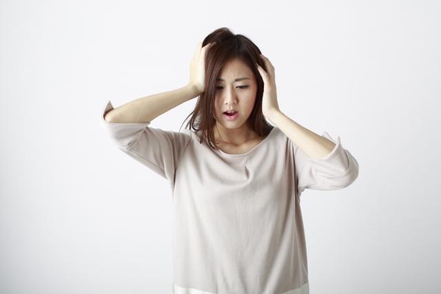 頭を抱え落ち込む女性