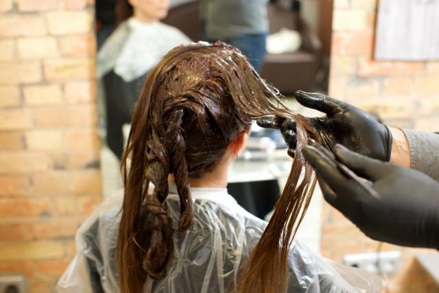 美容室でカラーリングの施術を受けている女性