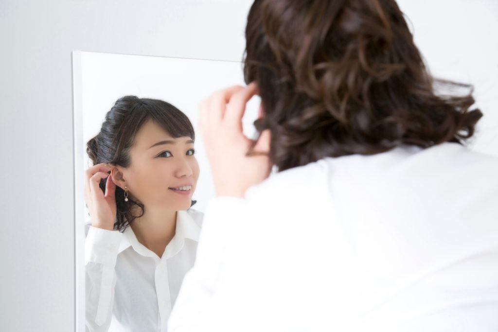 鏡で髪をチェックしている女性