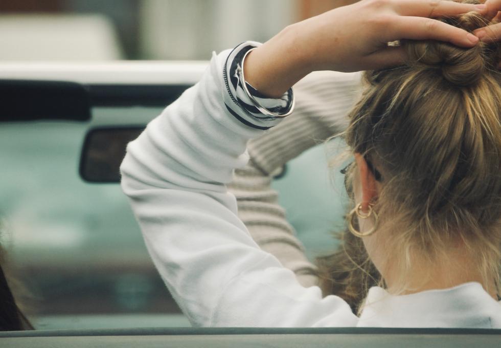 車で髪をヘアスタイルをチェックする女性