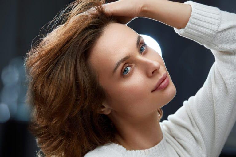 髪をかき上げるモデル
